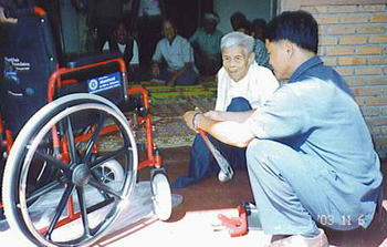 Our oldest member (87 years) in Chiangdao looking on why his new wheelchair is being assembled.
